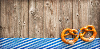 Rustic background for Oktoberfest. With Bavarian white and blue fabric and pretzels royalty free stock photo