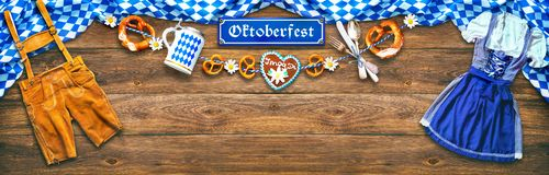 Rustic background for Oktoberfest. With white and blue fabric, Bavarian clothes, gingerbread, beer stein and pretzel royalty free stock photo