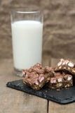 Rustic background with rocky road dessert squares with glass of. Rocky road squares on rustic background with glass of milk Stock Image
