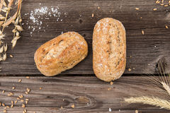 Rustic baguette and wheat on an old vintage wood table. Stock Photos