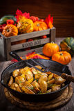 Rustic baked potatoes with herbs and pumpkins Stock Photography