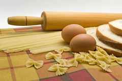 Rustic baking. Pasta spaghetti with eggs, bread and kitchen tools over rustic background Royalty Free Stock Image