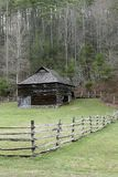 Rustic barn. A rustic barn and wooden fence near forest stock image