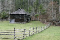 Rustic barn. A rustic barn and wooden fence near forest royalty free stock images
