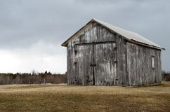 Rustic barn with dark clouds Royalty Free Stock Photos