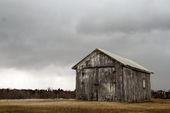 Rustic barn with dark clouds Stock Images