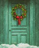 Rustic barn door with Christmas wreath. Rustic green barn door with Christmas wreath Stock Photo