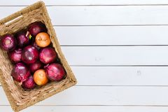 Rustic basket with a mix of red and brown onions. Rustic wicker basket with a mix of healthy fresh red and brown onions viewed from above on a white wood Royalty Free Stock Photography