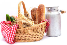 Rustic basket with vegetables and bread, and milk jug old Stock Photos