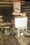 Rustic bathhouse. Inside with wood stove and basin Royalty Free Stock Photo