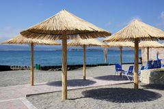 Rustic beach umbrellas and chairs on shore of lake Stock Images