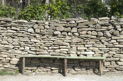 Rustic bench in front of a stone wall Royalty Free Stock Image