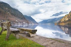 Rustic benches on lakeshore. Travel destinations theme image with the Dachstein Mountains reflected in the water of the Hallstatter lake and wooden benches on stock images