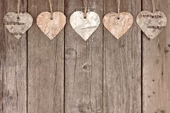 Rustic birch bark heart ornaments hanging against wood Royalty Free Stock Photos