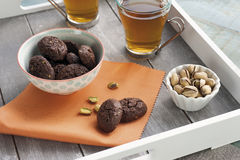 Rustic biscuits with chocolate and nuts in ceramic cup. Served on wooden tray with two cups of tea and a cup of fresh pistachio nuts Royalty Free Stock Photos