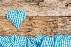 Oktoberfest background with blue fabric heart and blue checked frame stock photos