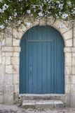 Rustic blue wooden door with white flowers above stock photo