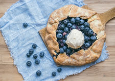 Rustic blueberry pie on a wooden board and white tissue Royalty Free Stock Images