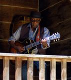 Rustic Blues. Blues musician, Wes Mackey playing guitar on rustic cabin porch Royalty Free Stock Images