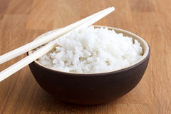 Rustic bowl of white rice on modern wood surface. Royalty Free Stock Photos