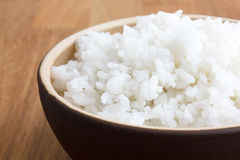 Rustic bowl of white rice on wood surface. Royalty Free Stock Images
