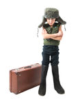 Rustic boy in a fur hat and boots standing near an old suitcase with his hands crossed Royalty Free Stock Images