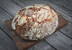 Rustic bread. A rustic bread loaf on a breadboard Royalty Free Stock Photography