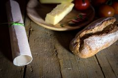 Rustic bread and cheese on a wooden table, parchment scroll. Rustic bread and cheese with tomatoes and radishes on a old wooden table, parchment scroll Royalty Free Stock Images