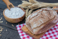 Bakery Bread on a Wooden Table. Rustic  bread, flour on Wooden bowl, wheat and cutting board and picnic cloth on vintage wood table Stock Images