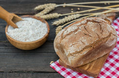 Bakery Bread on a Wooden Table. Rustic  bread, flour on Wooden bowl, wheat and cutting board and picnic cloth on vintage wood table Royalty Free Stock Photo