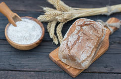 Bakery Bread on a Wooden Table. Rustic bread, flour on Wooden bowl, wheat and cutting board on vintage wood table Royalty Free Stock Photos
