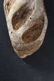 Rustic bread loaf on Black Slate Board. Royalty Free Stock Photography