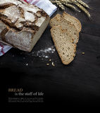Rustic bread loaf and slices on dark wood fading to black, sampl Royalty Free Stock Photography