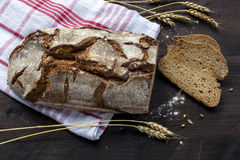 Rustic bread loaf and slices with wheat ears on a dark wooden ta Stock Photo