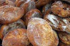 Rustic bread loaves piled for market. Fresh baked rustic bread loaves stock image