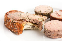 Rustic bread spread with pate,  bite missing. Stock Images