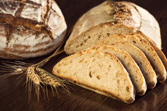 Rustic bread and wheat on a dark brown fundal Royalty Free Stock Images