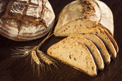 Rustic bread and wheat on a dark brown fundal Royalty Free Stock Image