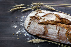 Rustic bread and wheat on a dark wooden table Royalty Free Stock Image