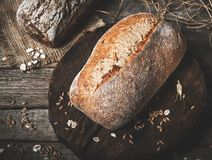 Rustic bread and wheat on an old vintage planked wood table. Dar. K moody background with free text space royalty free stock photos