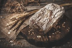 Rustic bread and wheat on an old vintage planked wood table. Dar. K moody background with free text space stock photos