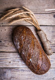 Rustic bread and wheat on an old vintage planked wood table. Dark moody background with free text space. And stock image