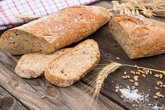 Rustic bread and wheat on an old vintage wood table. Royalty Free Stock Images