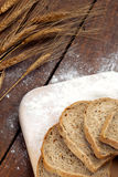 Rustic bread and wheat on an old vintage wood table Royalty Free Stock Images