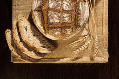 Rustic bread and wheat on a traditional cloth Stock Image