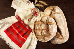 Rustic bread and wheat on a traditional girl costume Stock Images