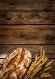 Rustic bread and wheat on vintage wood table Royalty Free Stock Image