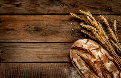 Rustic bread and wheat on vintage wood table. Rustic bread and wheat on an old vintage planked wood table. Dark moody background with free text space Stock Photos
