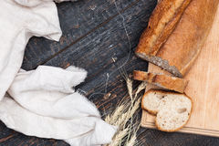 Rustic bread on wood table. Dark woody background with free text space. The macro view of rustic bread on an old vintage wooden table. Dark woody background stock photography