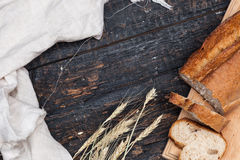 Rustic bread on wood table. Dark woody background with free text space. The macro view of rustic bread on an old vintage wooden table. Dark woody background stock images